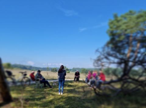 Die Gruppe der mutigen Spaziergang sitzt mit genügen Abstand in einem Halbkreis unter schattenspendenden Bäumen. Der Himmel ist fast wolkenlos und der Sandmagerrasen wirkt trocken.