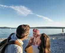 Julia und ihr Mann stehen mit dem Rücken zur Kamera. Julia hebt ihr Baby hoch und küsst es auf die Wange. Das Baby lacht. Im Hintergrund der Familie sieht man das Meer, einen Kiesstrand und eine Inselkette.