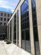 Ein Gebäudeteil des modernisierten Lorenzer Pfarrhofs mit grauen Steinplatten und verglaster Fensterfront über 2 Stockwerke, in denen sich die umliegenden Gebäude und der Himmel spiegeln.